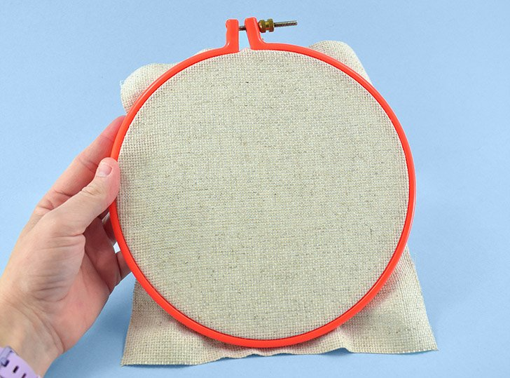 "Place your foundation material in an 8"" embroidery hoop. Pull the fabric to be as taut as possible within the frame."