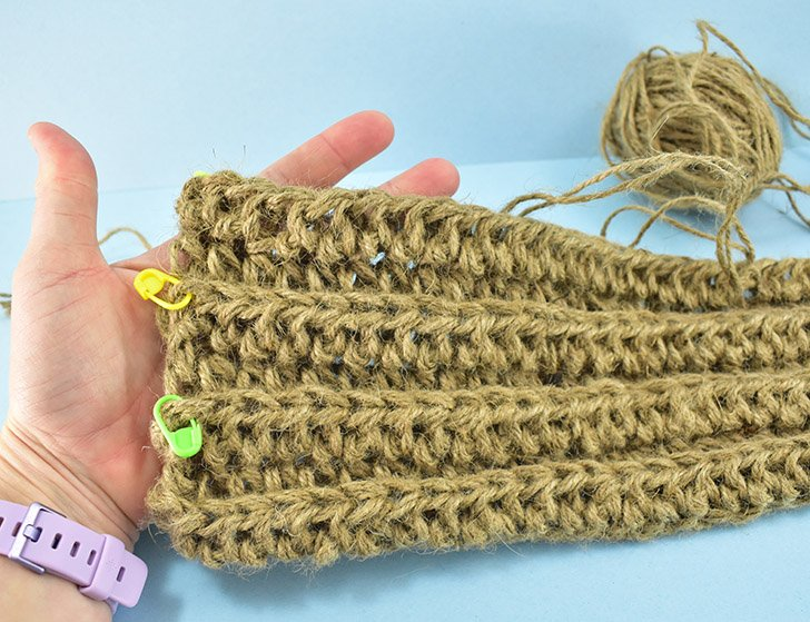 Continue these 55 half double crochet stitches down the length of the jute rug until you reach the stitch marker from the previous row. That is the last stitch you will crochet into. Chain twice and turn your work. Continue stitching until your rug is around 22″ x 26″ (for me that was 32 rows).
