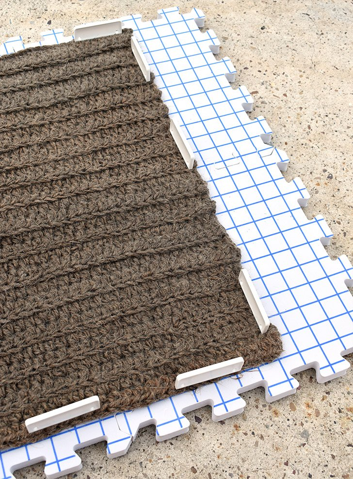 Using the lines on your blocking mats pull to stretch the rug so that it matches a rectangular shape. Push blocking comes into the outer stitches so that the rug will hold its shape. Allow to fully dry. Speed up the drying process by allowing to dry outside, however, the sun might lighten the jute on the one side facing up.