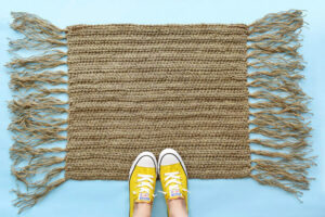 Continue to add tassels evenly to both sides of the crochet rug. Trim to desired length.