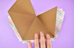 Fold the piece into its 3d form and place the glued section to the patterned paper. Before the glue sets, be sure that the piece has been well placed and the full front will be covered by the paper.