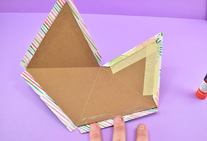 Wrap the extra paper over the edge onto the back of the chipboard. Glue down and/or use tape to secure in place.