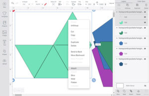 """The front piece of each pocket has lines that need to be either scored or drawn onto the chipboard. Select the light green shape with the lines on top of it and isolate it from the other shapes. Right click and select """"Attach""""."""