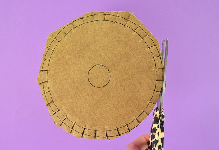 Using a pair of sharp scissors cut each slot around the DIY Kumihimo disk first. Next trim around the outer circle to form the disk-shape.