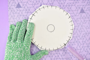 (Follow the first 4 steps of the cardboard disk tutorial) Print out your PDF pattern and cut the disk shape out along the outermost circle. Place on top of your foam and trace the circle using a felt tip pen or fine tip marker. Cut the pattern down to the next circle and place it in the center of the first circle you drew. Follow the lines on the pattern to draw the cord slots around the disks edge. Cut the pattern down to the innermost circle, place in the center of the foam and trace. Using a sharp craft knife trim away the excess foam from the outer circle. Next use the craft knife to cut the slots around the disk's outer edge. Cut away the inner circle with the craft knife as well.