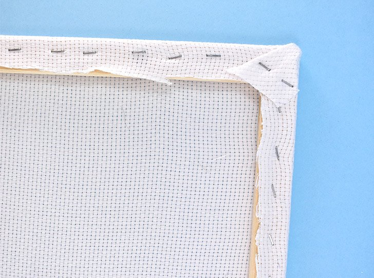 Wrap Monk's cloth over the frame and use a staple gun to secure it.