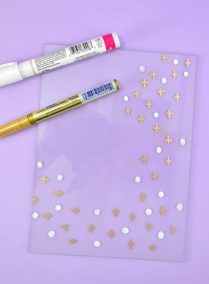 Using your gold and white paint markers paint a flourish of dots, crosses, xs, or other simple shapes in a flourish.