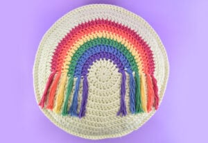 Looking for a fun, colorful, and fringed DIY addition to your decor? Get the free pattern and hook up this round crochet rainbow pillow!