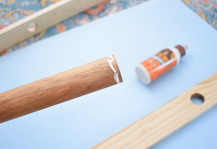 Lay one side of the ladder on a flat work surface. Apply a thin line of glue just to the very end of one dowel.