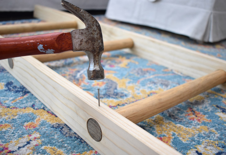 Using a hammer, tap a trim nail into the hole you created. Repeat for all of the rungs on both legs of the ladder.