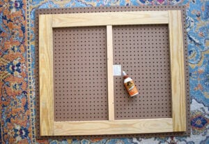 "Lay your pegboard on a flat surface. Arrange your cut wood like so. The shorter 31"" boards are on the short sides of the pegboard. The longer 32"" boards are placed inside of the side boards along the top and bottom (longer side) of the pegboard. Lastly, the shortest 26""  piece is a little extra support placed in the center."