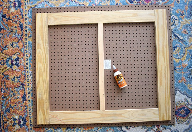 """Lay your pegboard on a flat surface. Arrange your cut wood like so. The shorter 31"""" boards are on the short sides of the pegboard. The longer 32"""" boards are placed inside of the side boards along the top and bottom (longer side) of the pegboard. Lastly, the shortest 26"""" piece is a little extra support placed in the center."""