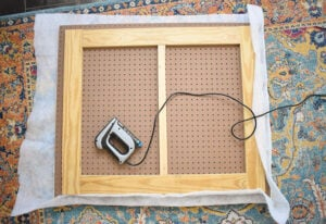 "Place quilt batting on your work surface and then the headboard on top with the support wood facing you. Trim so that you have 4-5"" of batting on all sides. Fold the batting over and staple in place onto the pegboard. Fold at the corners and use several staples to tack it down with as little bulk as possible. Use sharp scissors to trim away the excess."
