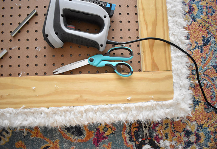 Repeat the process with the faux fur material but tack it to the side of the wood frame rather than to the pegboard.