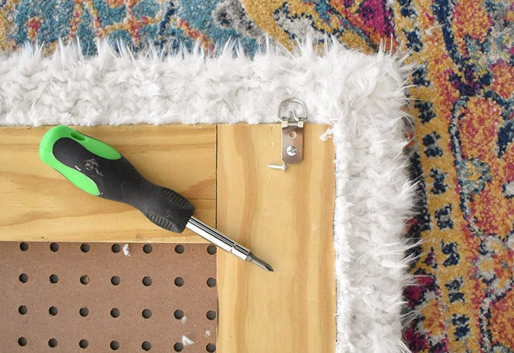 Using screws attach large D hooks to the top and back side of the faux fur headboard. Make sure the bottom loop of the D hook is even with the top edge of the wood. (This will make the headboard easier to hang.)