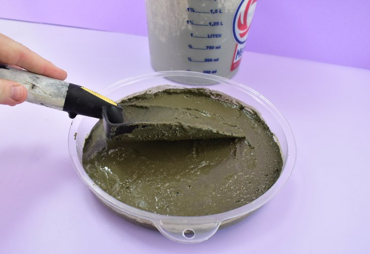 Gently spoon your cement into the mold taking care not to shift the shelf liner and glass below.
