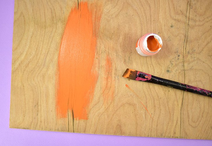 "Cut a thin piece of plywood down to 11"" x 24"" and paint with orange chalk paint. Allow to dry."