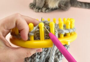 Use your loom knitting tool to pull all of the loops off of the loom.