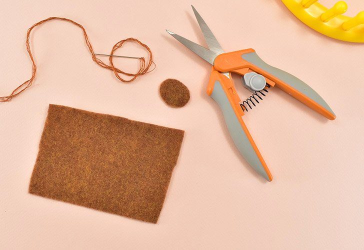 """From a piece of brown felt cut a circle approximately the size of a quarter and a rectangle that measures 2"""" x 3.5"""". Thread and embroidery needle with matching floss."""