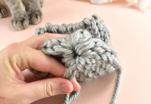 Once you've run the yarn through all loops remove the needle. Pull both ends of the yarn piece tight to close the bottom of the loom knit pumpkin like a drawstring bag.