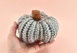 To finish your pumpkin make a few small stitches at the bottom center to secure. Run the needle up through the inside of the pumpkin and out of the side. Pull the yarn taut and snip close.