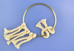 Pull the 2 legs of the cord over the brass hoop and through the curve of the cord.