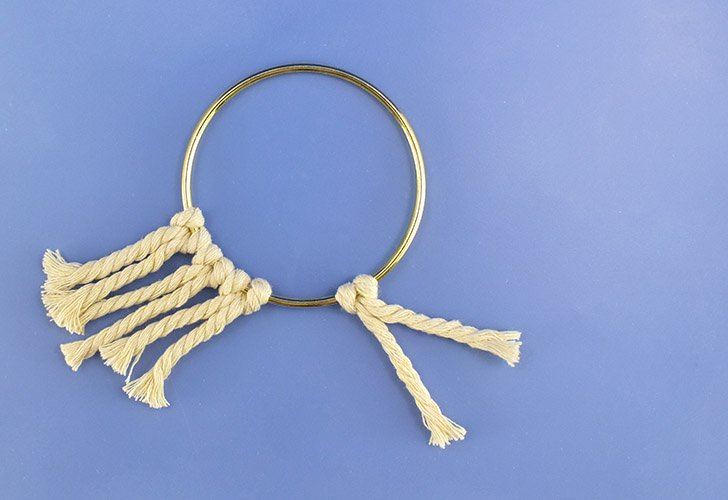 Pull both legs of the cord down one at a time to tighten the knot onto the ring.