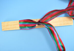 Create a loop with your ribbon and place it inside of the 2 dowels.