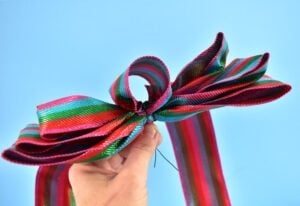 The next option is to form a loop from the ribbon. The size of this loop will greatly depend on the size of your ribbon, bow, etc. Form the loop and secure with glue, if you feel it is necessary. Run wire through the loop and secure onto the bow twisting the ribbon together on the back side.