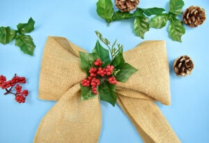 My favorite way to finish DIY bows is to hot glue something in the middle. You can use fake flowers, ornaments, or even floral picks among other things.