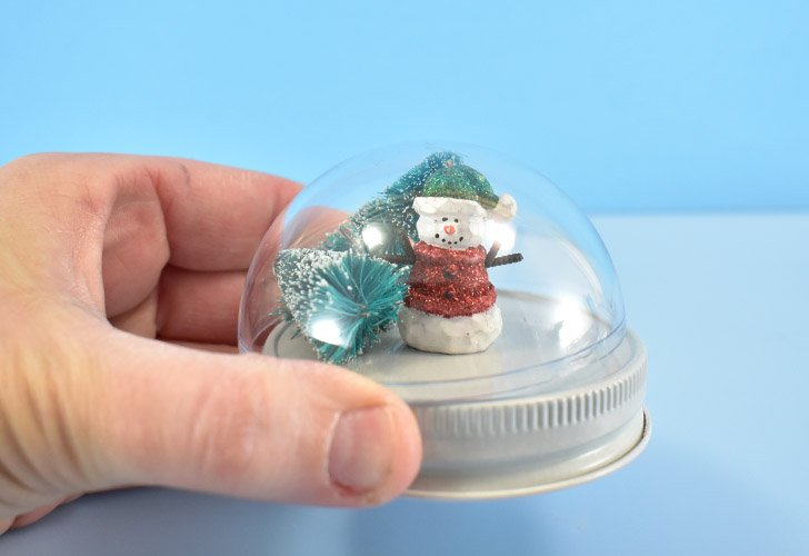 It's a good idea to make sure that your mini ornaments will fit inside of the globe before any glue is introduced. Bottle brushes can be trimmed down to the right size using a wire cutters. More solid ornaments will need to fit from the get go.