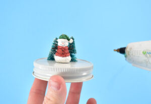 Once happy with the size and placement of your snow globe elements, glue in place on top of the lid with hot glue.
