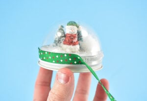 Once you're happy that the two pieces are being held together well enough to stay put without your help, flip the entire thing over. Hot glue Christmas ribbon so that it overlaps the seam where the ornament and lid meet. Continue around until the side of the lid is covered down to the lip.