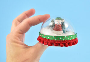 Add a piece of pom pom trim around the ornament over the ribbon to finish.