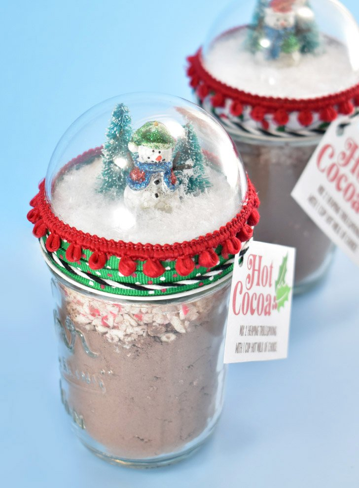 Looking for an adorable and fun gift to give this winter? Fill Snow Globe Mason Jars with our Hot Cocoa Recipe. So easy, so sweet!