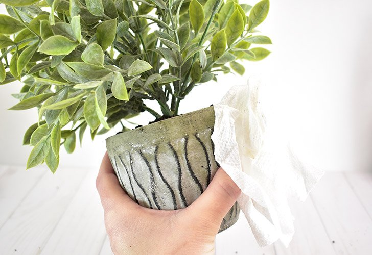 Remove the fake dirt from the pot and leaves before it dries.