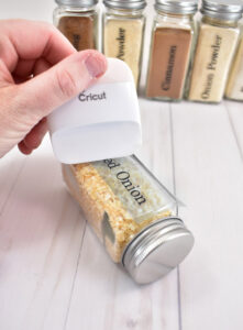 Place the transfer tape and vinyl decal onto a spice jar. Use the scraper to apply pressure to help the vinyl adhere to the glass.
