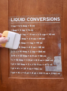 Carefully place the conversion chart as desired onto your door or binder. Use a scraper to apply pressure and transfer the vinyl onto its new surface.