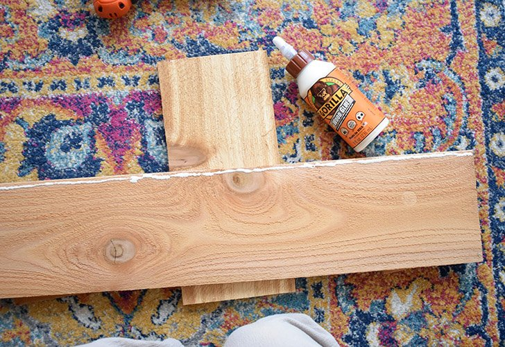 """Lay one 24"""" board flat on your work surface. Squeeze a thin line of glue to the board as pictured above."""
