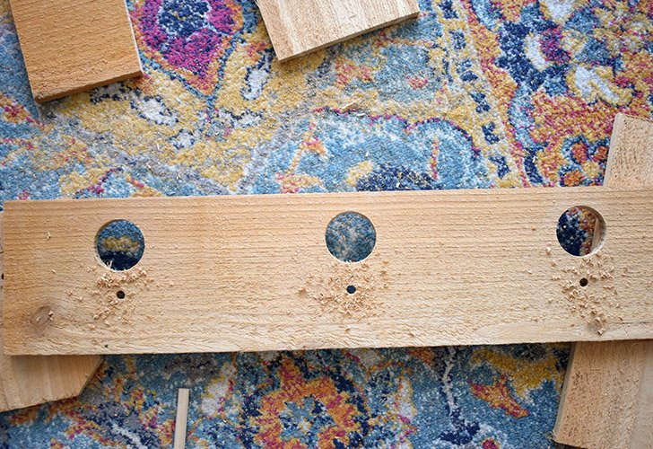 """From the left side of one 24"""" board measure and mark at 4"""", 12"""", and 20"""" all 2"""" from the top of the board. Drill a 1"""" hole in these spots. Drill a 5/16"""" hole 1 inch down from larger."""