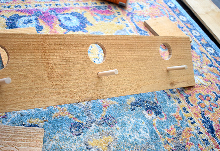 """Place a trace of wood glue inside of the smaller holes beneath the larger. Tape the 3"""" wood dowels into each of these holes. Gently use a hammer or mallet, if necessary, to place the dowels firmly inside of the holes."""