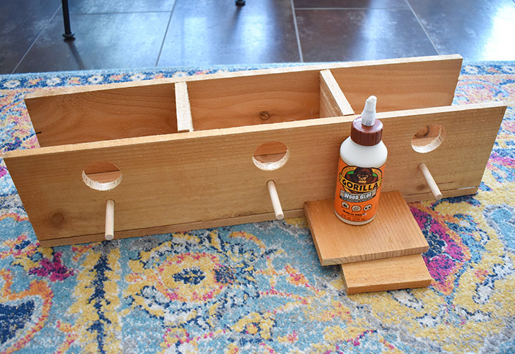 Glue the board with perches into place as seen here. Add 3 screws from the bottom to hold in place.