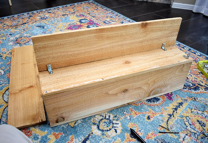 """To begin forming the planter, place a 24"""" board on top of the birdhouse block as shown and glue together."""