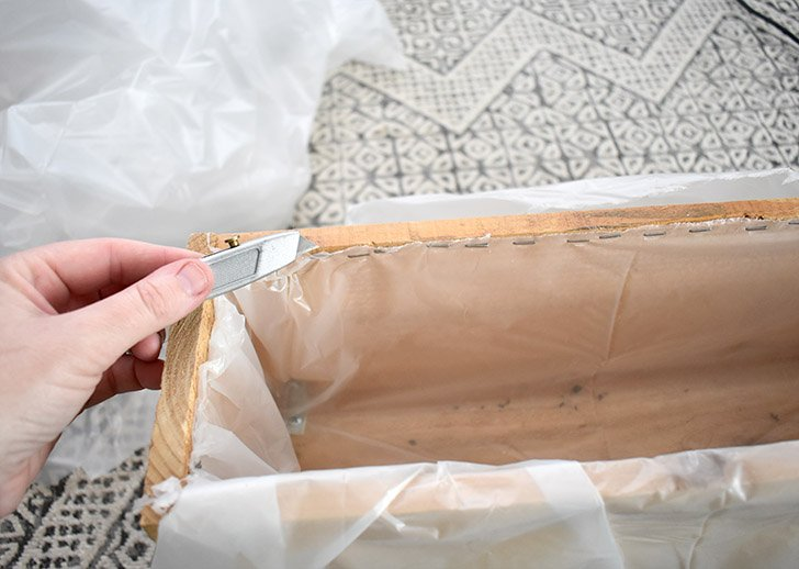 Using a staple gun, tack the material into place a half an inch below the edge of the planter. Use a sharp utility knife and carefully trim away the excess.
