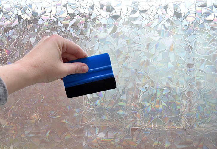 Working from the the center outward, like a sunburst, use your felt covered squeegee to apply the film to the window and remove any air bubbles or water.