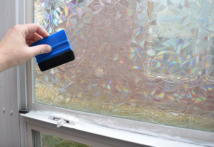 Once the vinyl is cut to fit, use your squeegee to apply the edges and corners well. If necessary, you can gently pry up the film and spray soapy water beneath to help application.