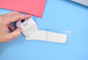 Use ascraper to apply pressure to the transfer tape to transfer the vinyl onto it. Gently pull away the transfer tape. Apply more pressure to any letter that isn't transferring to the tape.