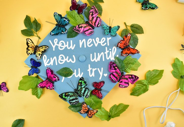 Start pushing the leaves of artificial greenery around and under the butterflies and glue down.