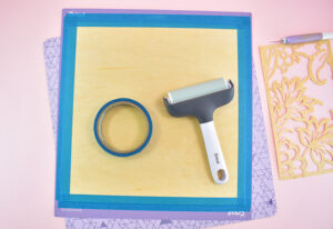 Apply a piece of veneer to a StrongGrip cutting mat. Use a brayer to fully attach the wood and then tape around the edges to ensure it stays in place during cutting.