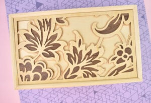 Place the largest, bottommost piece of the inlay design inside of the beveled lid. Since no 2 jewelry boxes will have the exact same shape inside, you might need to trim a little bit with a pair of scissors to get the piece to fit neatly inside the space.